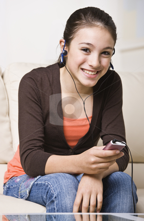 Smiling Teenager Listening to Music stock photo, A happy young teenager listening to an MP3 music player.  She is smiling at the camera.  Vertically framed shot. by Jonathan Ross