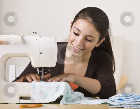 Beautiful Girl Sewing stock photo, A beautiful, smiling young girl sewing on a sewing machine.  Horizontally framed shot. by Jonathan Ross