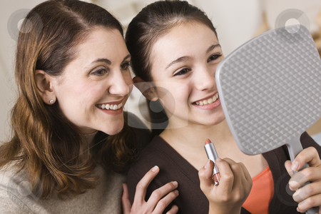 Smiling Mother and Daughter with Lipstick, Looking at Mirror stock photo, A beautiful young girl holding a mirror and a tube of lipstick with her mother.  They are smiling.  Horizontally framed shot. by Jonathan Ross