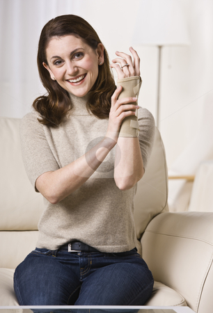 Woman Putting on Wrist Brace stock photo, A woman is seated on a living room sofa and putting on her wrist brace.  She is smiling at the camera.  Vertically framed shot. by Jonathan Ross