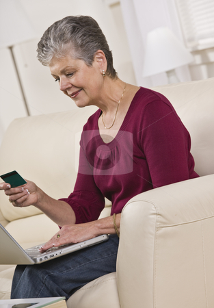 Woman on Laptop stock photo, An elderly woman is seated in a couch with a laptop.  She is looking at a card in her hand and smiling.  Vertically framed shot. by Jonathan Ross