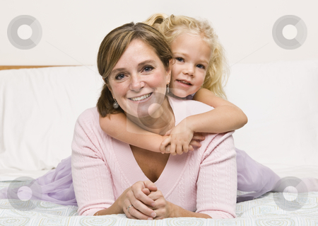 Mother and Daughter Cuddling on Bed stock photo, A mother is lying with her daughter on her bed.  The girl has her arms aroung her mother and they are smiling at the camera.  Horizontally framed shot. by Jonathan Ross