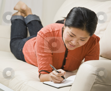 Woman Writing in Book stock photo, A woman is laying on the couch and writing in a book.  She is smiling and looking away from the camera.  Horizontally framed shot. by Jonathan Ross