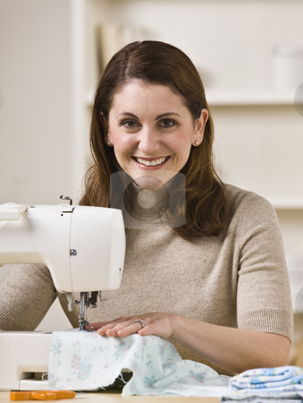 Smiling Woman Using Sewing Machine stock photo, A beautiful woman sewing on a sewing machine and smiling at the camera.  Vertically framed shot. by Jonathan Ross