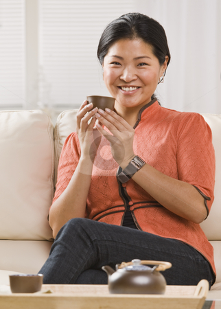 Woman Drinking Tea stock photo, A woman is seated on her sofa, and drinking tea out of a tea cup.  She is smiling at the camera.  Vertically framed shot. by Jonathan Ross