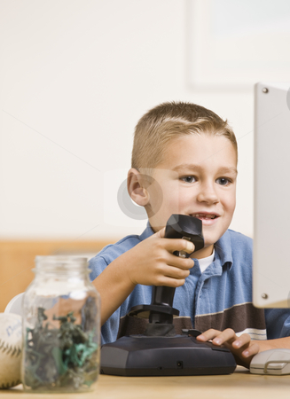 Boy Playing Computer Games stock photo, A young boy is playing computer games.  He is smiling and looking at the screen.  Vertically framed shot. by Jonathan Ross