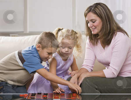Woman Playing with Children stock photo, A mother is playing checkers with her young children.  They are looking away from the camera.  Horizontally framed shot. by Jonathan Ross