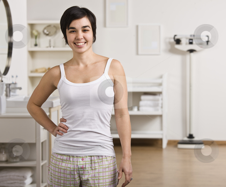 Woman in Bathroom stock photo, A young woman is standing in her bathroom and smiling at the camera.  Horizontally framed shot. by Jonathan Ross