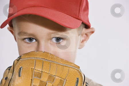 Boy with Mitt and Baseball Cap stock photo, A young boy is wearing a baseball cap and holding a baseball mitt up to his face.  Horizontally framed shot. by Jonathan Ross
