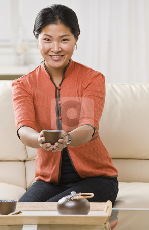 Woman Holding Tea stock photo, A woman is holding a cup of tea out in front of her.  She is smiling at the camera.  Vertically framed shot. by Jonathan Ross
