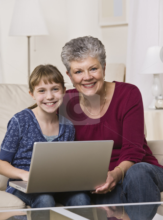 Grandmother and Granddaughter Online stock photo, A grandmother and her young granddaughter are working together on a laptop.  Vertically framed shot. by Jonathan Ross