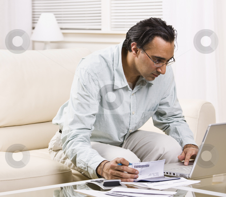 Man Paying Bills With Laptop stock photo, A man paying his bills online.  He has a checkbook in his hand.  Square framed shot. by Jonathan Ross
