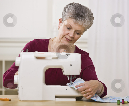 Senior Woman Sewing stock photo, A senior woman sewing on a sewing machine in her home.  Horizontally framed shot. by Jonathan Ross