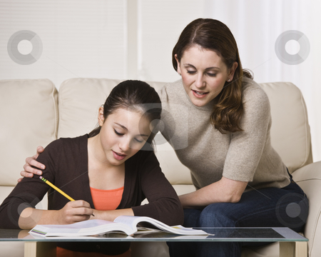 Woman Helping Daughter with Homework stock photo, A mother is helping her young daughter with her homework.  They are looking away from the camera.  Horizontally framed shot. by Jonathan Ross