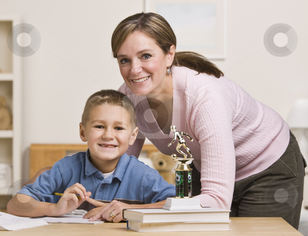 Woman Helping Son with Homework stock photo, A mother is helping her  young son with his homework.  They are both smiling at the camera.  Horizontally framed shot. by Jonathan Ross