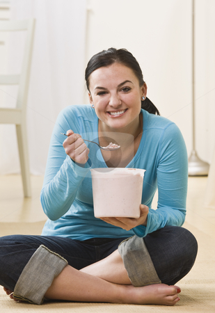 Woman Eating Ice Cream stock photo, A young woman is sitting on the floor and eating ice cream out of a tub.  She is smiling at the camera.  Vertically framed shot. by Jonathan Ross