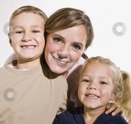 Mother and Children Smiling at Camera stock photo, A young mother is standing with her two young children and they are smiling at the camera.  Square framed shot. by Jonathan Ross