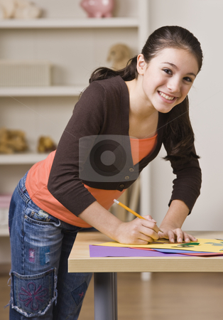 Girl Working on Project stock photo, A young girl is working on a project and smiling at the camera.  Vertically framed shot. by Jonathan Ross