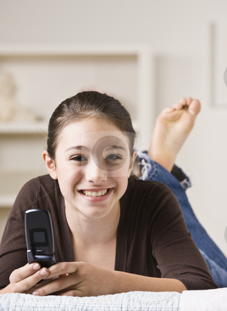 Smiling Teenager Holding Cellphone stock photo, A smiling young teenager lying on her bed and holding a cellphone.  Vertically framed shot. by Jonathan Ross