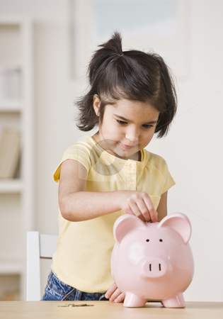 Girl With Piggy Bank stock photo, A young girl is playing with a piggy bank.  She is looking away from the camera.  Vertically framed shot. by Jonathan Ross