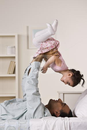 Father Playing with Daughter stock photo, A man is laying on a bed and holding up his baby daughter.  They are smiling at each other.  Vertically framed shot. by Jonathan Ross