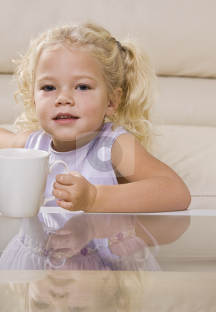 Girl Drinking out of Mug stock photo, A young girl is sitting at the coffee table and drinking out of a mug.  She is looking at the camera.  Vertically framed shot. by Jonathan Ross