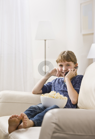 Girl Talking on Cellphone stock photo, A young girl is seated on the living room sofa with a bowl of popcorn and is talking on a cell phone.  She is smiling at the camera.  Vertically framed shot. by Jonathan Ross