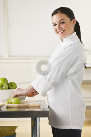 Woman Slicing Apples stock photo, A young woman is slicing apples in a kitchen.  She is smiling at the camera.  Vertically framed shot. by Jonathan Ross