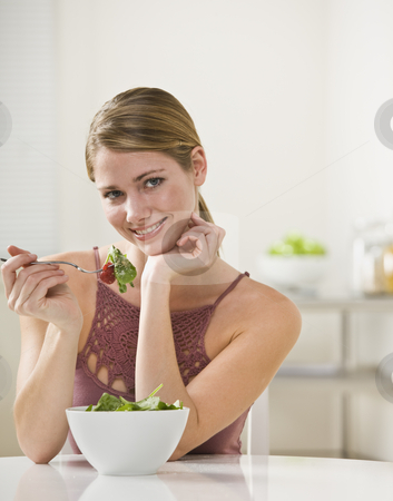 Woman Eating Salad stock photo, A young woman is eating salad and smiling at the camera.  Vertically framed shot. by Jonathan Ross