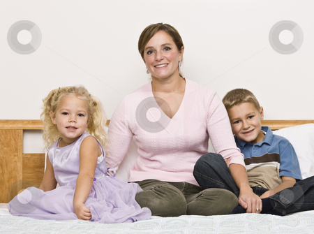 Mother and Children Sitting on Bed stock photo, A mother sits on a bed with her son and daughter as they smile at the camera. Horizontally framed shot. by Jonathan Ross