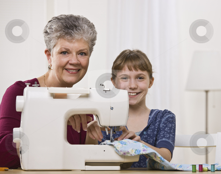 Grandaughter Sewing with Granddaughter stock photo, A young girl is sewing with her grandmother in the living room.  They are smiling at the camera.  Square framed shot. by Jonathan Ross