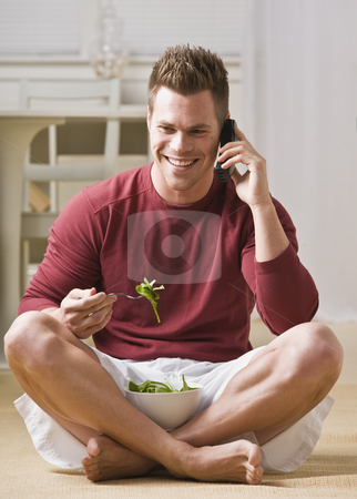 Man With Cell Phone and Salad stock photo, A man is talking on a cell phone and eating a salad.  He is smiling and looking away from the camera.  Vertically framed shot. by Jonathan Ross