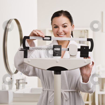 Woman Checking Weight stock photo, A young woman is standing on a bathroom scale and checking her weight.  She is smiling at the camera.  Square framed shot. by Jonathan Ross