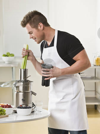 Man Using Juicer stock photo, A young man is using a juicer in a kitchen.  Vertically framed shot. by Jonathan Ross