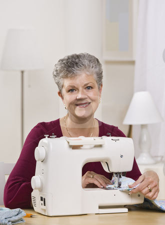 Woman on Sewing Machine stock photo, An elderly woman is working on a sewing machine in her home and smiling at the camera.  Vertically framed shot. by Jonathan Ross