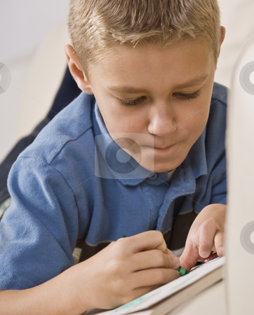 Boy Coloring in Book stock photo, A young boy is laying on his stomache and coloring in a coloring book.  He is looking away from the camera.  Vertically framed shot. by Jonathan Ross