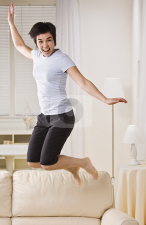 Woman Jumping on Couch stock photo, An excited woman is jumping up and down on the living room sofa.  She is smiling at the camera.  Vertically framed shot. by Jonathan Ross