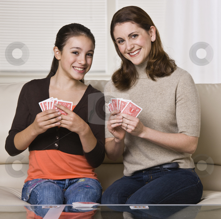 Mother and Daughter Playing Cards stock photo, A young mother and her daughter are playing cards together.  They are smiling at the camera.  Square framed shot. by Jonathan Ross