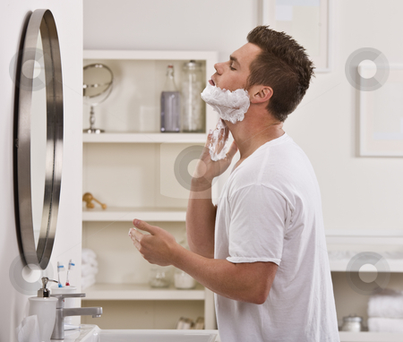 Man Shaving Face stock photo, A man is shaving his face in the mirror.  He is looking away from the camera.  Horizontally framed shot. by Jonathan Ross