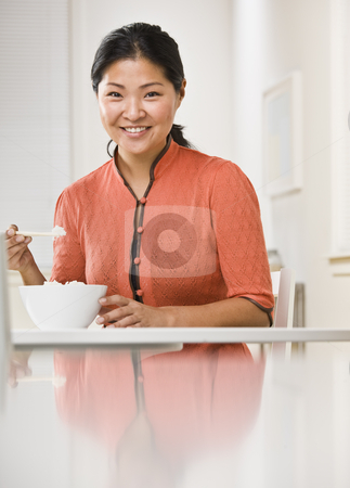 Woman Eating Bowl of Rice stock photo, A woman is eating a bowl of rice at the kitchen table and smiling at the camera.  Vertically framed shot. by Jonathan Ross