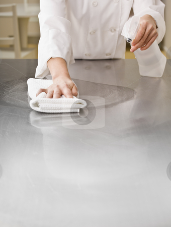 Chef Cleaning Counter stock photo, A chef is cleaning a counter in a professional kitchen with a bottle of solution and a rag.  Vertically framed shot. by Jonathan Ross