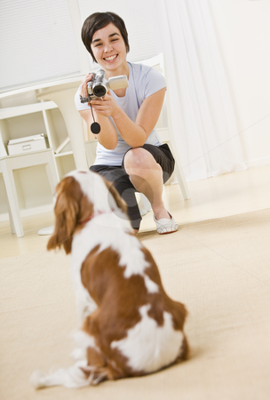 Woman Taking Picture of Dog stock photo, A young woman is taking a picture of her dog.  She is smiling and looking away from the camera.  Vertically framed shot. by Jonathan Ross