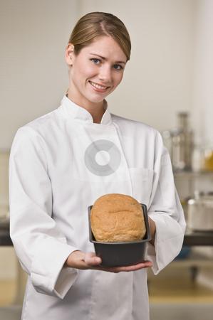 Baker with Loaf of Bread stock photo, A young woman is standing in a kitchen and holding out a loaf of bread.  She is smiling at the camera.  Vertically framed shot. by Jonathan Ross