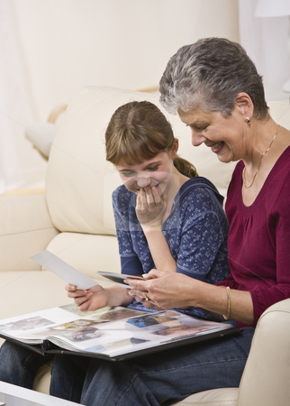 Grandmother and Granddaughter Looking at Photos stock photo, A grandmother looking through a photo album with her granddaughter.  They are both smiling.  Vertically framed shot. by Jonathan Ross