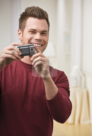 Man Holding Camera stock photo, A young man is holding up a digital camera and smiling at the camera. Vertically framed shot. by Jonathan Ross