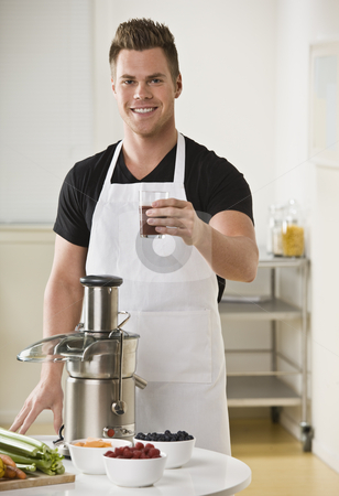 Man Using Juicer stock photo, A young man is standing in his kitchen and making juice from a juicer.  He is smiling at the camera.  Vertically framed shot. by Jonathan Ross
