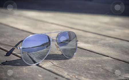 Sunglasses stock photo, Sunglasses on a bridge reflecting the sun by Fredrik Elfdahl