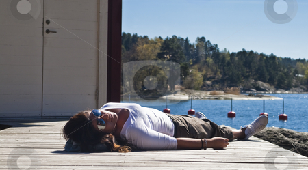 Girl on a pier stock photo, Girl laying on a pier by Fredrik Elfdahl