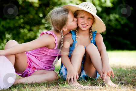 Kiss on my sisters cheek stock photo, Two little girls in fresh colors in the park by Frenk and Danielle Kaufmann