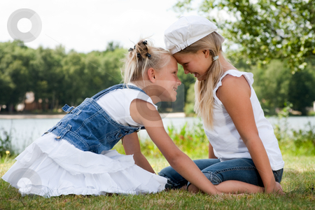 Head hugs and smiling stock photo, Two little girls in fresh colors in the park by Frenk and Danielle Kaufmann
